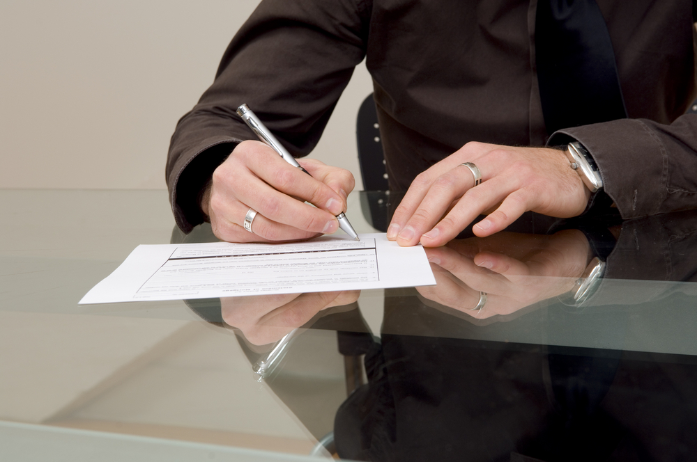 man signing commercial landscape maintenance contract