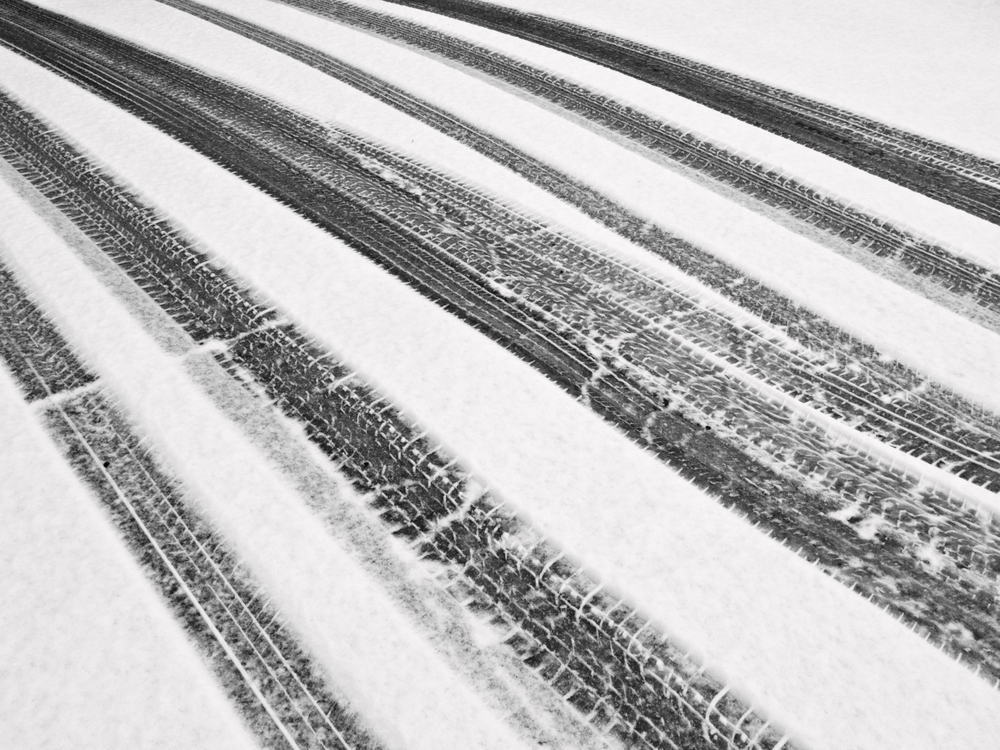 Winter at a glance, in black and white Recent tire tracks through snow on ramp to garage