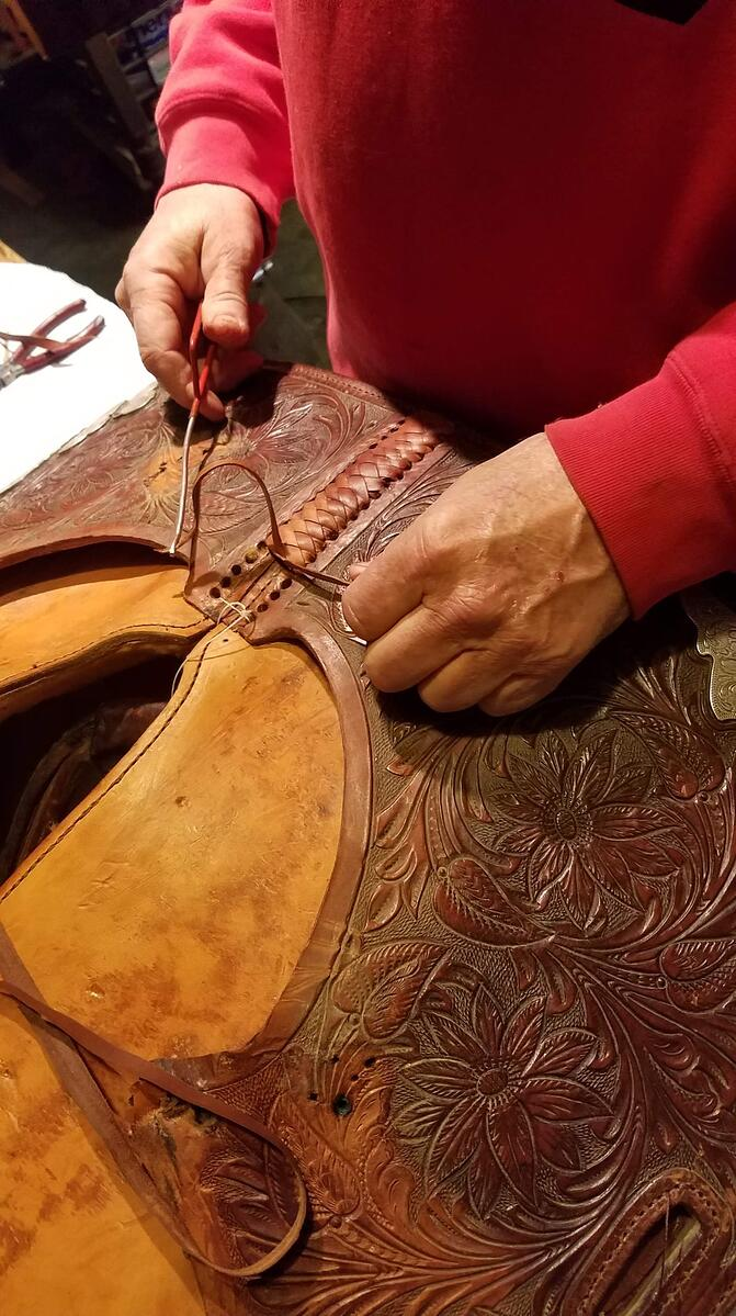 Tommy Neergaard stitching a leather saddle