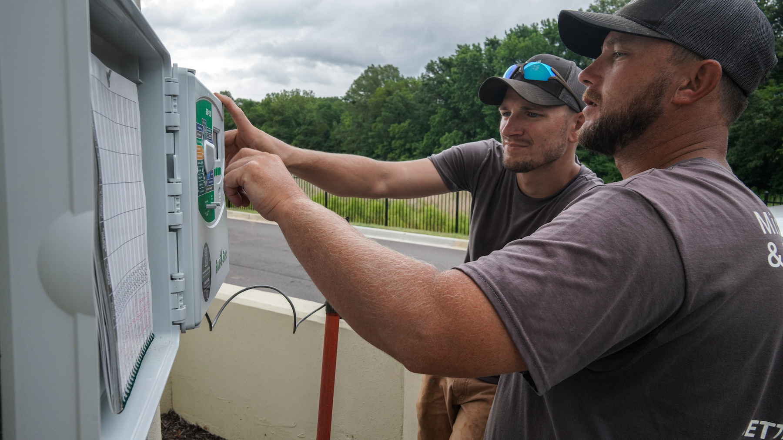 irrigation crew adjusting irrigation system controller