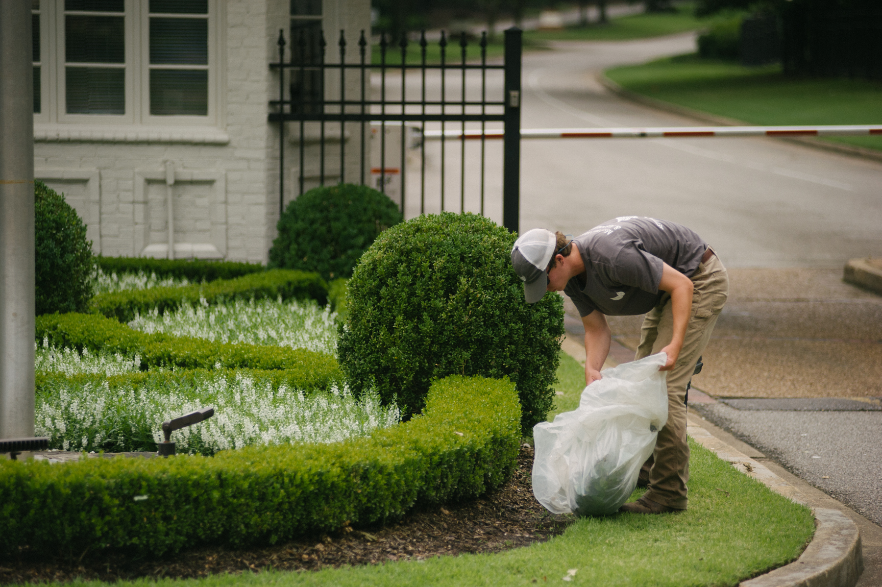 Commercial landscaping team cleaning up trash