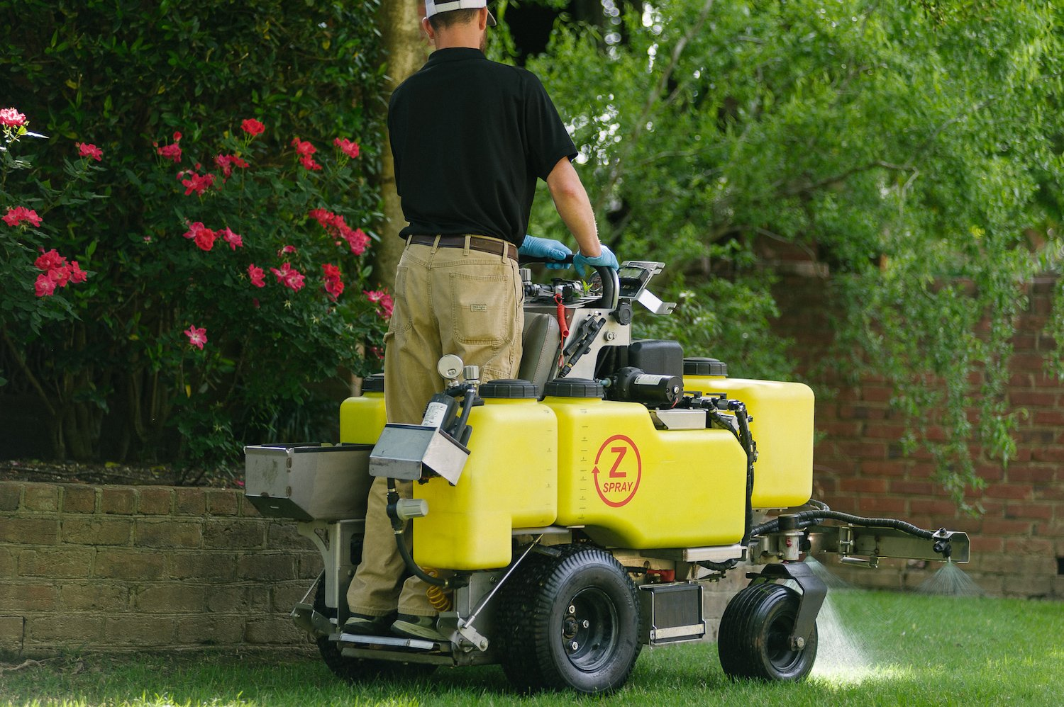 commercial landscaping technician spraying lawn