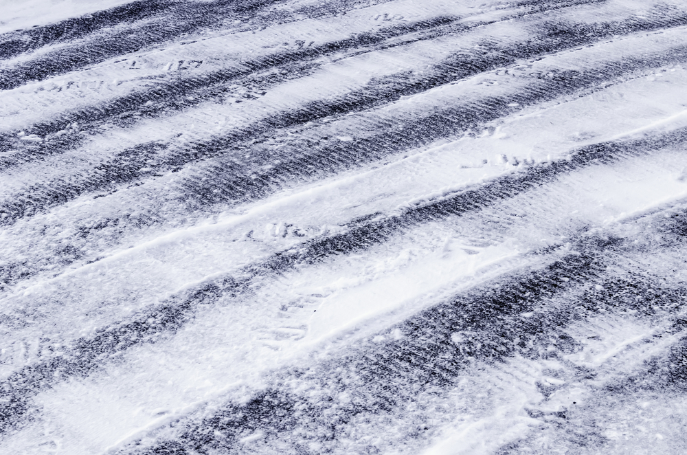 Winter abstract Rows of tread marks from tires of small plow in snow on asphalt driveway in northern Illinois