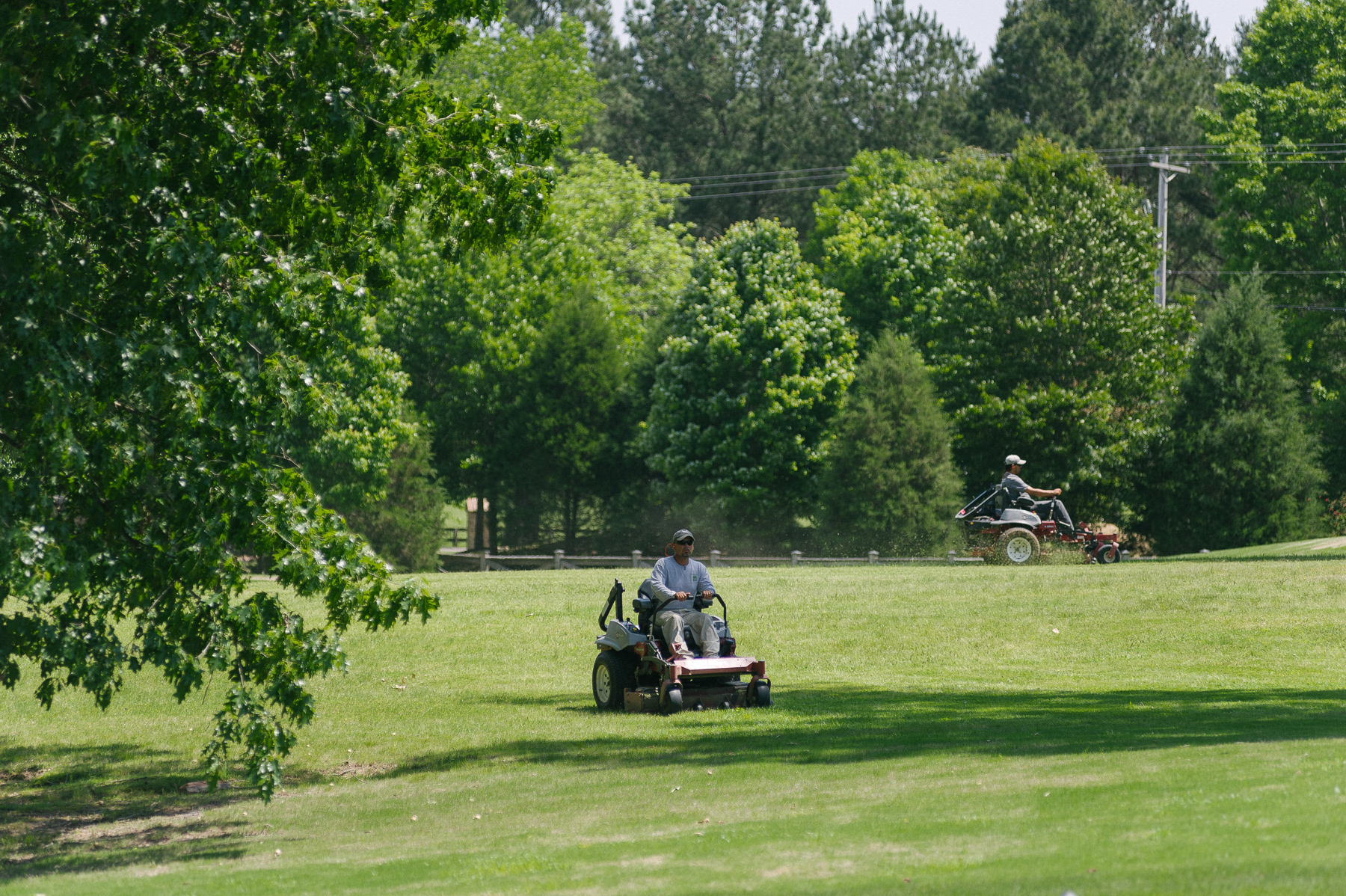 Professional landscape technician mowing commercial property